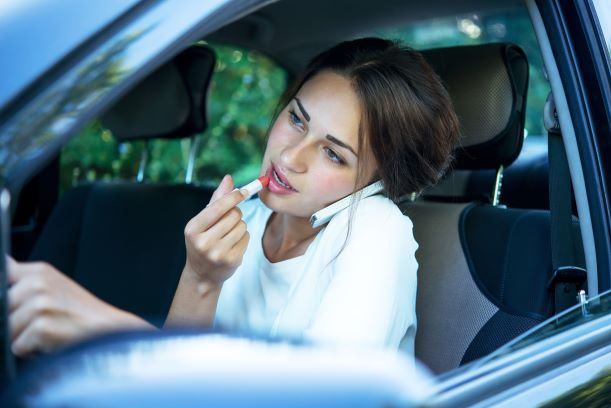 Girl applying lipstick on the phone - Distracted driver